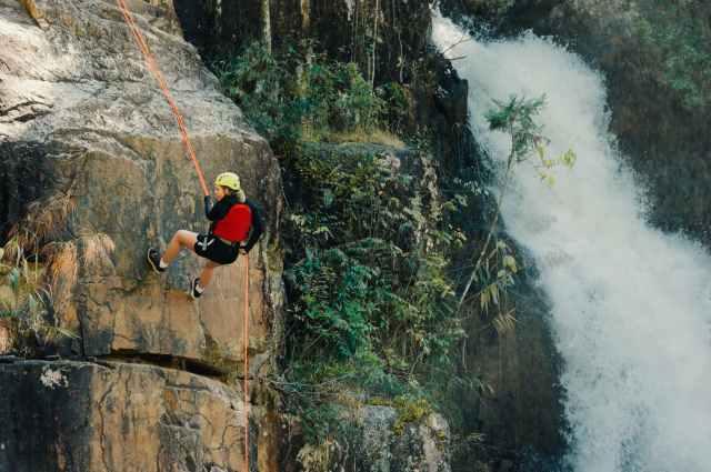 woman rocking climbing near waterfalls