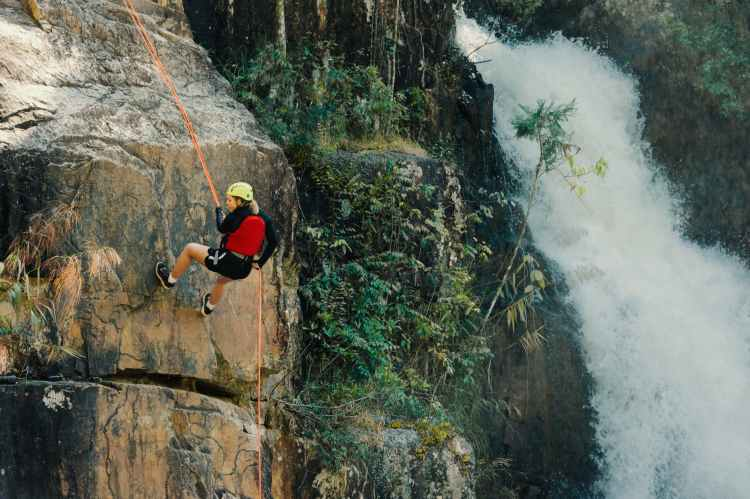 woman rocking climbing near waterfalls