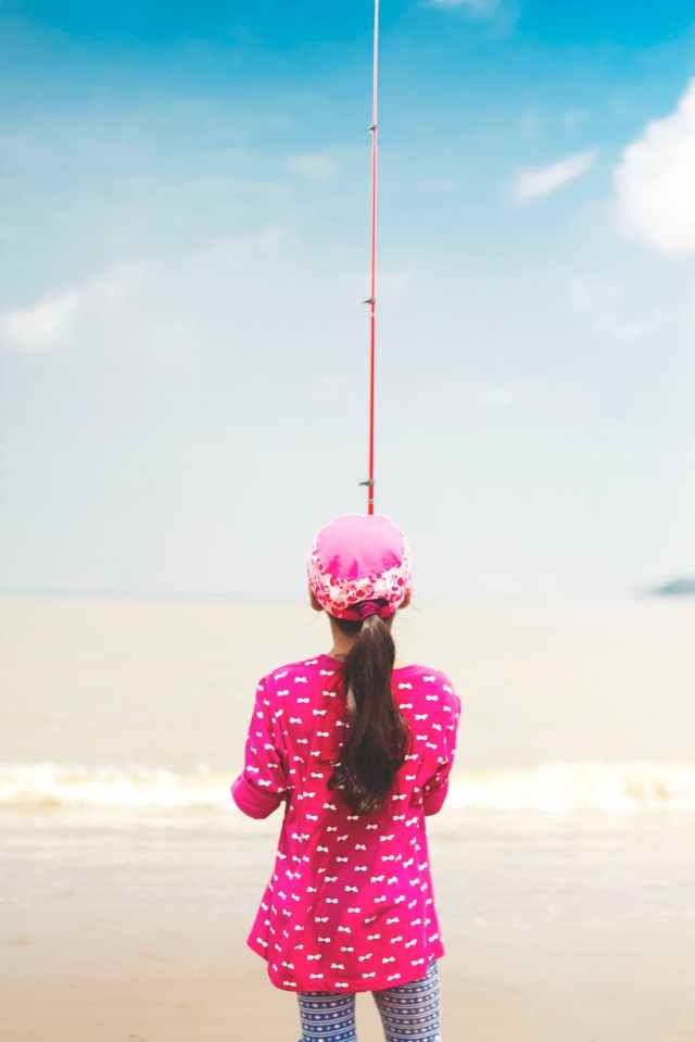 woman in pink long sleeved shirt holding red fishing rod