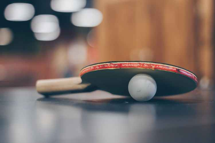 selective focus photo of table tennis ball and ping pong racket
