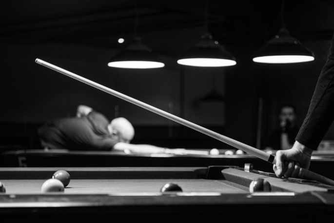 grayscale photo of man holding cue stick
